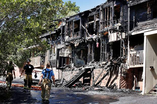 Durango Fire Protection District firefighters collect their gear Wednesday afternoon at the Tercero Townhouse units after battling a fatal early morning fire at 2123 West Third Ave.