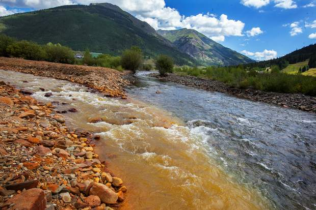 Mine waste tinged water in Cement Creek from the Gold King Mine area flows into the Animas River in August 2015 in Silverton. Scientists who have studied the impact of the mine spill on the watersheds will present findings at a June 20-22 conference in Farmington.