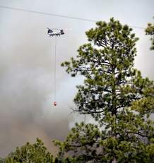 A Chinook Helicopter with a bucket on Thursday heads towards the structures in the community of Ruby Hole, New Mexico.