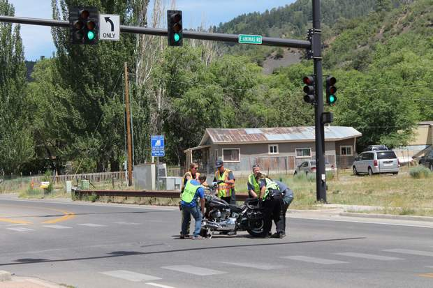 Emergency responders move a motorcycle that was damaged in a crash near the intersection of Florida Road and East Animas Road.