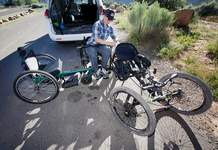 "Rosa Malloy-Post talks about the differences of the ""GRIT Freedom Chair,"" left, and her mountain bike on Rim Trail on Thursday. The GRIT wheelchair designed to better navigate rough terrain was awarded to her and she said it should work well for camping, river trips and festivals."