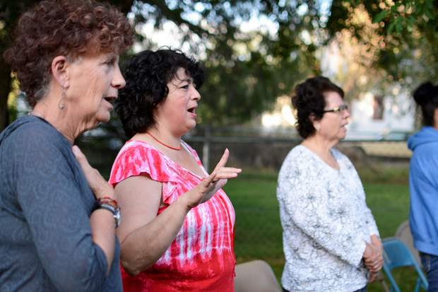 Rosa Sabido, center, sings along during a candlelight vigil Sunday at the United Methodist Church in Mancos.