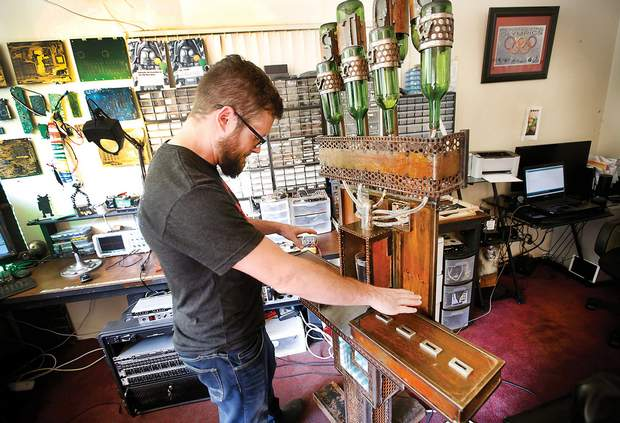 Ryan Finnigan plays his invention Benny the Booze Organ in his living room, which also functions as an electronics lab. Finnigan builds novelty robots in addition to running a metal art company. He is also one of the founders of the MakerLab.