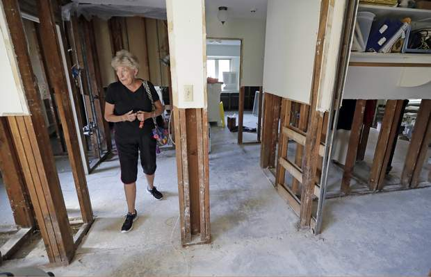 In this Monday, Sept. 11, 2017, photo, Arlene Estle looks at the damage to her home which was flooded in the aftermath of Hurricane Harvey, in Houston. Victims of Harvey, desperate to rebuild their homes and lives, are facing the harsh reality that it may take months for an overwhelmed construction industry to address their needs. (AP Photo/David J. Phillip)