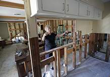 In this Monday, Sept. 11, 2017, photo, Arlene Estle talks about the damage to her home caused by floodwaters from Hurricane Harvey, in Houston. Victims of Harvey, desperate to rebuild their homes and lives, are facing the harsh reality that it may take months for an overwhelmed construction industry to address their needs. (AP Photo/David J. Phillip)