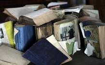 In this Monday, Sept. 11, 2017, photo, books damaged by floodwaters sit on a table inside the home of Arlene Estle, which was damaged by floodwaters from Hurricane Harvey, in Houston. Victims of Hurricane Harvey, desperate to rebuild their homes and lives, are facing the harsh reality that it may take months for an overwhelmed construction industry to address their needs. (AP Photo/David J. Phillip)