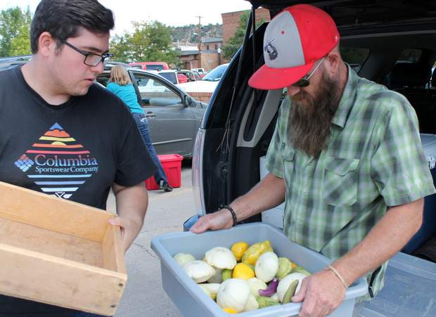 Issac Otero, a volunteer with Cooking Matters, and Darrin Parmenter, Colorado State University extension agent, collect food from the Durango Farmers Market Saturday for the Produce Bounty project. Durango Farmers Market vendors also donate to Manna regularly.